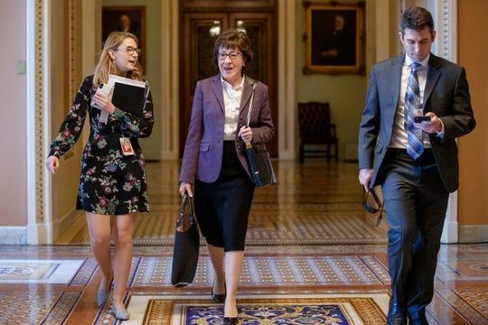 Sen. Susan Collins, R-Maine, (center) walks through the Ohio Clock Corridor in the U.S. Capitol on Jan. 27 in Washington, DC.