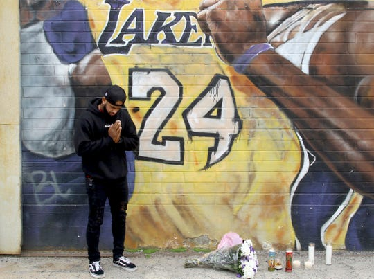 A fan pays respects at a mural of Kobe Bryant in an alley in downtown Los Angeles.