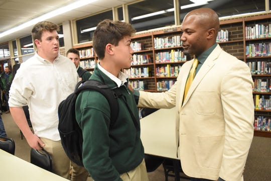 Justin Charles (right) talks to some of his players after being introduced as the new football head coach for Holy Savior Menard High School in January.