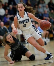 Xavier's Maggie McGinnis (13) drives to the basket against Menasha's Alayna Yost during a Bay Conference game earlier this season. McGinnis leads the Hawks in scoring this season.