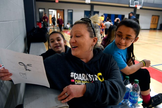 McKenzie Husing, (center), reads a note with her daughters, Jaedyn (left), 8, and Ciara, 10, during a basketball league practice Dec. 5 at First Baptist Church. Ciara Husing was playing in her first practice since undergoing surgery and treatments for cancer just below her left knee.