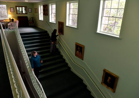 Tammi Briscoe takes a closer look at one of the portraits on the main staircase as Roxanne Schoen continues to the first floor of the Abilene Woman's Club on Tuesday. Schoen is teaching a genealogy class that meets in the historic building.