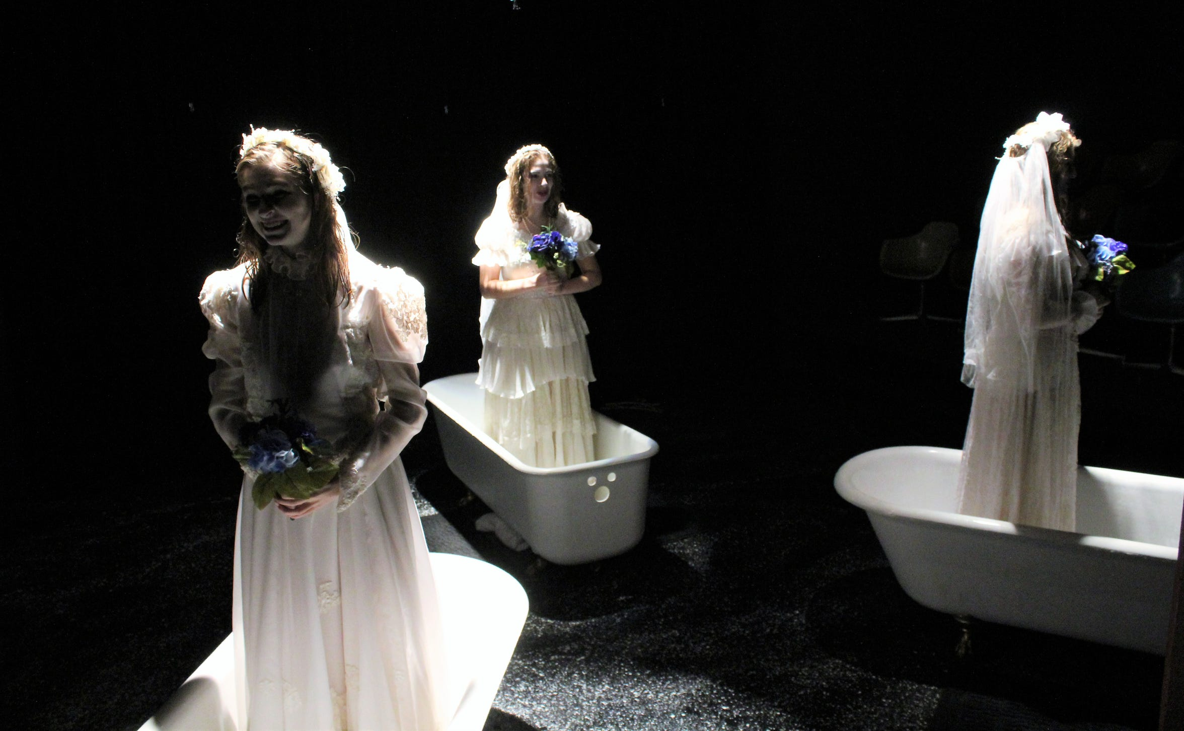 """Three deceased women arise from their bathtubs as brides - from left, Cassidy Davis, Bethany Soder and Bailee Barrett - to tell how they came to be drowned each time by their husband, George Joseph Smith, in this rehearsal scene from Hardin-Simmons University's student-directed """"The Drowning Girls,"""" which is on stage twice this weekend."""