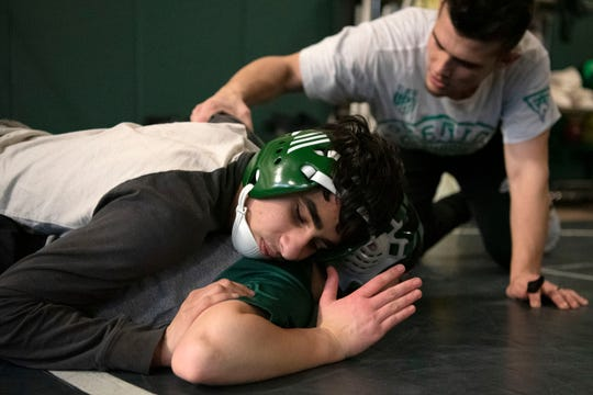 "Pennfield head coach Joey Ramos II guides varsity wrestler Nasko Cleland, who is blind, during practice on Friday, Jan. 24, 2020 at Pennfield High School in Battle Creek, Mich. ""I feel like I can be good at it because I can use feel and I don't need my vision,"" Clelend said."