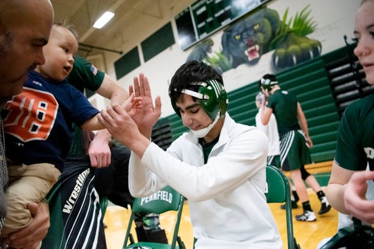 Pennfield varsity wrestler Nasko Cleland, who is blind, gives a high-five to two-year-old Easton Ramos on Wednesday, Jan 22, 2020 at Pennfield High School in Battle Creek, Mich.