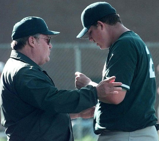 Rice coach Mike Pearo and pitcher Jamie Merchant, right, talk during a 1998 high school baseball game.