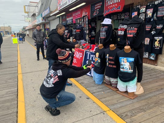 John Tansey Jr. of Kensington and Mia Floyd of Absecon take photos of some the Trump merchandise being sold on Wildwood's boardwalk ahead of President Donald Trump's rally on Jan. 28.