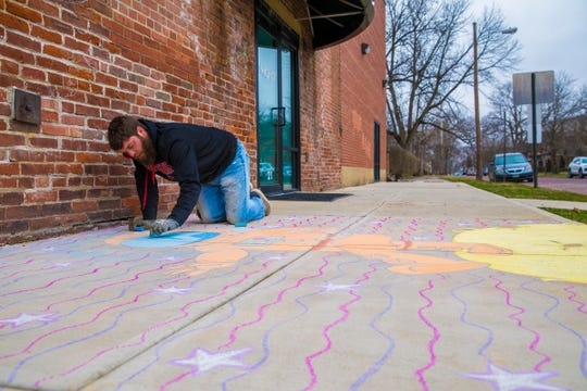 Local artist Kenneth Corcoran works on an astronaut inspired drawing outside of the Mighty Children's Museum in Downtown Chillicothe on Jan. 28, 2020. Corcoran has drawn various cartoon caricatures outside of businesses like Crispie Crème Donut Shop and hopes to put a smile on people's faces.