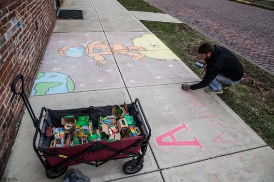 """Kenneth Corcoran looks on his phone to make sure he spelled """"astronaut"""" correctly as he finishes his cartoon chalk drawing outside the Mighty Children's Museum."""