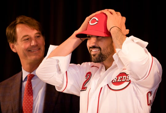 Nick Castellanos  puts on his Reds hat at his first press conference as a Reds outfielder on Tuesday, Jan. 28, 2020 at Reds Hall of Fame and Museum in downtown Cincinnati. Casellanos has agreed to terms on a 4-year, $64-million contract through the 2023 season.