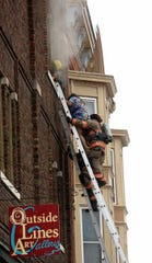 Emergency personnel rescues a woman from a building at the corner West 11th and Main streets in Dubuque, Iowa, on Monday, Jan. 27, 2020. Authorities say firefighters rescued four people from a fire that erupted in a downtown Dubuque building.