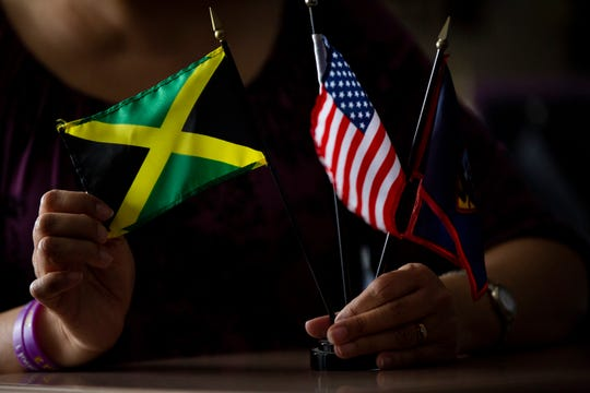 Kerisa Baedke, a Spanish teacher at Prairieview School, holds three flags: a Jamaican flag for her father, a Guamanian flag for her mother, and a U.S. flag for herself. Baedke said her multicultural family sparked her lifelong interest in travel and language.