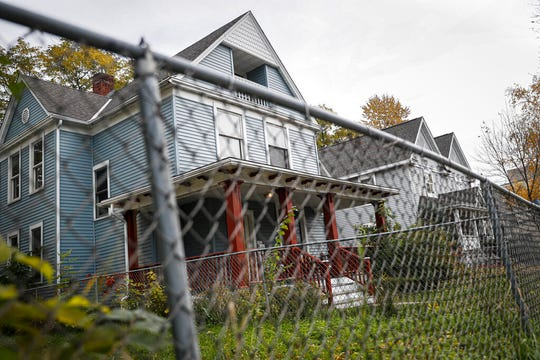 A fence surrounds the former home of Tyesha Edwards, an 11-year-old girl pierced in the heart by a stray bullet in 2002 while doing homework at her family's dining room table, Wednesday, Oct. 23, 2019, in Minneapolis.