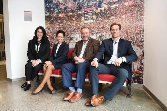 Zarah Broglin (from left), Vice-President, ODM Construction,  Rian English, Vice-President of Government Affairs and Community Relations, Keith Bradford, Senior Vice-President, Olympia Development of Michigan, and Stefan Stration, Vice President of Development, Olympia Development of Michigan,  have a seat on the original Joe Louis Arena stadium seats at Little Caesars Arena.