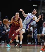 Cavaliers' Dante Exum works around Pistons' Svi Mykhailiuk, looking for a penalty, in the second quarter.