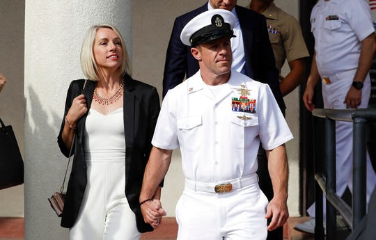 In this July 2, 2019, file photo, Navy Special Operations Chief Edward Gallagher, center, walks with his wife, Andrea Gallagher, as they leave a military court on Naval Base San Diego in San Diego.