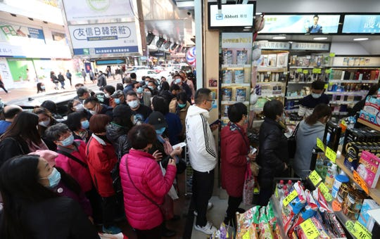 People queue up to receive free face masks outside a shop at Tsuen Wan in Hong Kong, Tuesday, Jan 28, 2020. China has confirmed more than 4,500 cases of a new virus. Most have been in the central city of Wuhan where the outbreak began in December.