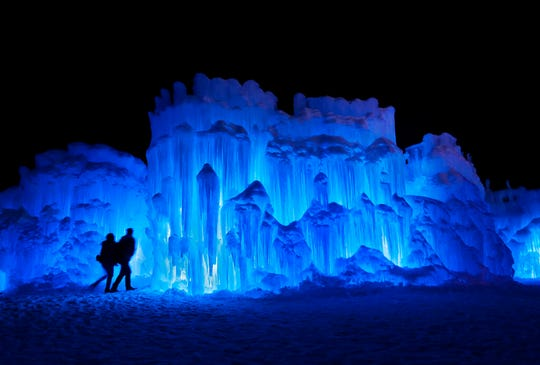 In this Saturday, Jan. 26, 2019 file photo, a couple heads toward an entrance to a cavern at Ice Castles in North Woodstock, N.H. A neighbor to the seasonal attraction alleges that melt water from the Ice Castles' property flooded her basement with over 15,000 gallons of water in April 2019.