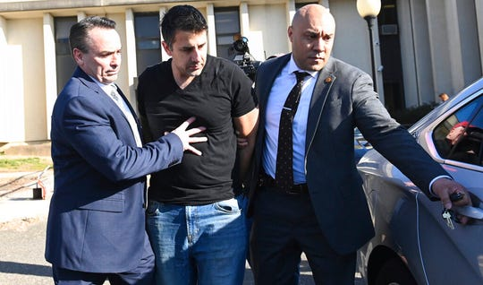 In this Jan. 24, 2020 photo, Michael Valva is led out of Yaphank police headquarters in Yaphank, N.Y. Valva is charged with second-degree murder in the death of his 8-year-old son, Thomas Valva, in Center Moriches, N.Y. It is alleged that the boy was forced to sleep in an unheated garage at the couple's home as temperatures dropped to under 20 degrees.