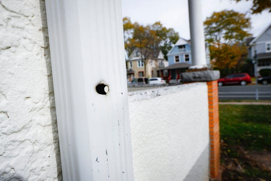 In this Oct. 23, 2019, photo, a bullet hole in a drainage vent cited in a crime scene investigation follows a trajectory towards the former home, in blue, of Tyesha Edwards, an 11-year-old girl pierced in the heart by a stray bullet in 2002 while doing homework at her family's dining room table in Minneapolis. Myon Burrell, a black teenager convicted for the killing with no gun, fingerprints or hard evidence implicating him, has drawn a growing number of legal experts, community leaders and civil rights activists who are worried that he may have been wrongly convicted.