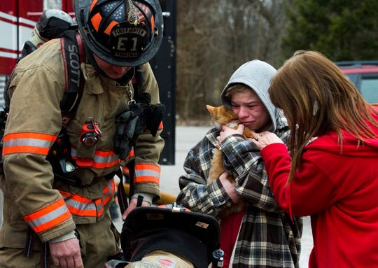 Cayden Wilkerson, 13, clutches his cat Lacy as Evansville firefighters ready a pet oxygen mask after a fire was sparked in their home at 501 Meyer Avenue in Evansville, Ind., Tuesday afternoon, Jan. 28, 2020. Everyone made it out of the home and firefighters shortly recused the cat after arriving on the scene.