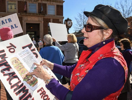 Lee Turner of Greenville looks at protest material while standing with the Tell Them Tuesday demonstration group on South Main Street in Greenville January 28. The group of democrats decided to stand with signs expressing concern about President impeachment trial hearings.