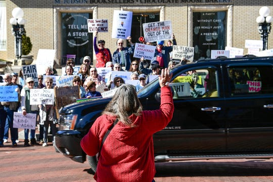 The Tell Them Tuesday demonstration group waves to the driver waving at them on South Main Street in Greenville January 28. The group of democrats decided to stand with signs expressing concern about President impeachment trial hearings.