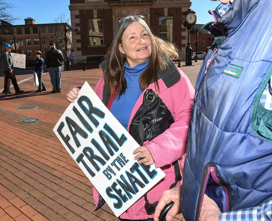 """Deb Morrow of Spartanburg carries a sign """"Fair Trial by the Senate"""" as the Tell Them Tuesday demonstration group stands on South Main Street in Greenville January 28. The group of democrats decided to stand with signs expressing concern about President impeachment trial hearings."""