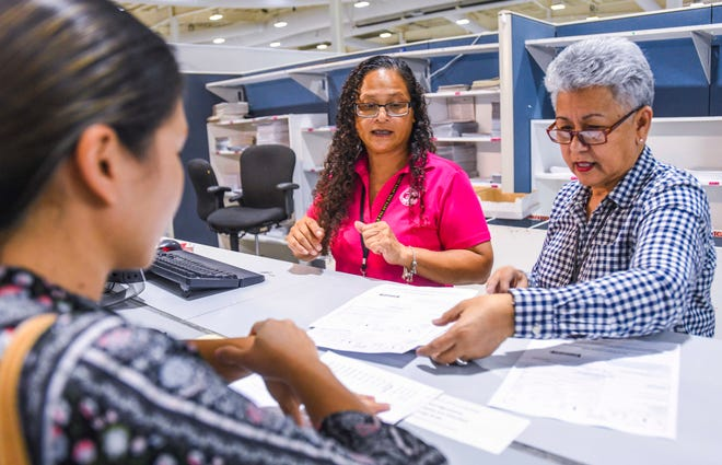 Income Tax Specialists Lorna Mansapit, center, and Becky Gamboa assist a customer at the Income Tax and Processing Branch window in the Department of Revenue and Taxation at Barrigada in this Jan. 28 file photo.
