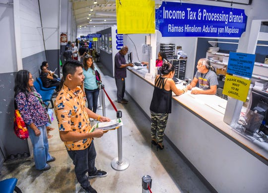 Customers line up and wait to be served at the Income Tax and Processing Branch window at the Department of Revenue and Taxation in Barrigada on Tuesday, Jan. 28, 2020.