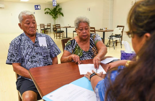 War survivors Manuel, left, and Rosa Benavente, are assisted by Debra-Jean Cruz, a personnel specialist with the Office of the Governor, during the couple's visit to the Guam War Claims Processing Center in Tamuning on Tuesday, Jan. 28, 2020.