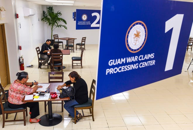 Dorothy Blas, lower left, a staff assistant with the Office of the Governor, assists a claimant in preparing her paperwork during her visit to the Guam War Claims Processing Center in Tamuning on Tuesday, Jan. 28, 2020.