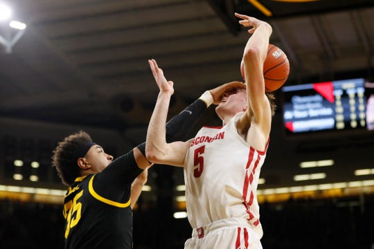 It was a rugged Big Ten Conference basketball game in Iowa City on Monday. Here, Iowa forward Cordell Pemsl (left) tries to block a shot by Wisconsin forward Tyler Wahl during the first half.