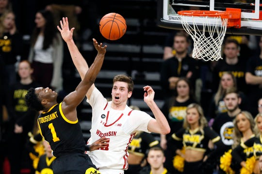 Iowa guard Joe Toussaint (1) is fouled by Wisconsin forward Nate Reuvers while driving to the basket during the first half of an NCAA college basketball game, Monday, Jan. 27, 2020, in Iowa City, Iowa. (AP Photo/Charlie Neibergall)