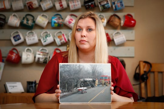 Kira Hudson, a survivor of two car crashes involving distracted driving and cellphones, holds a photo taken of her first accident, at her Carmel home, Friday, Jan. 24, 2020. Hudson was paralyzed after she crashed while talking on her cellphone while driving. Years later, she was hit by another distracted driver talking on their own cellphone.