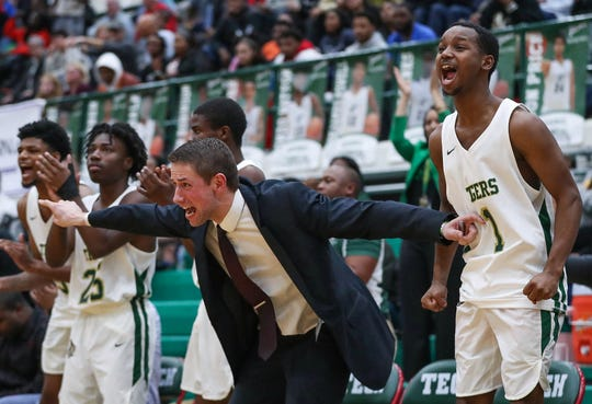 Players and coaches on the Crispus Attucks bench celebrate their lead during the second overtime period at Arsenal Technical High School in Indianapolis on Monday, Jan. 27, 2020. Crispus Attucks defeated Cathedral 94-91 in double OT to earn its first City tournament title since 1962.