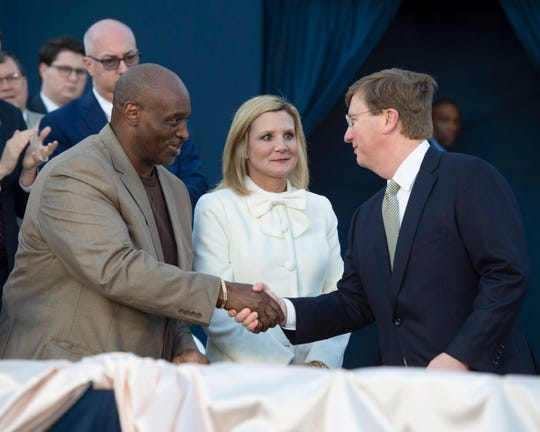 Recently inaugurated Miss. Governor Tate Reeves (right) shakes hands with Pastor Eddie Spencer (left) as First Lady Elee Reeves (center) watches. Gov. Reeves had just taken then stage to deliver his first State-of-the-State address from the steps of the Capitol in Jackson, Miss. on Monday evening. Spencer, a former inmate at Parchman, gave the benediction at the inauguration of Reeves as governor earlier this month. Monday, Jan. 27, 2020.Monday, Jan. 27, 2020.