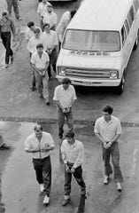 George Malvaney (center front) and the other nine mercenaries involved with the Bayou of Pigs plot entering the Orleans Parish Prison, April 1981.