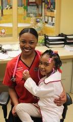 Family Scholar House graduate Jasmine, now a nurse, with daughter Brooklynn, a future nurse.
