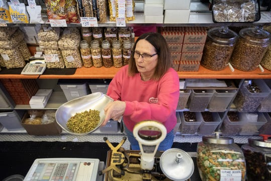 Tammy Melser, owner of The Peanut Shop in downtown Lansing weighs out pepitas Monday, Jan. 27, 2020.   Melser's father Floyd began working in the store in 1948 and purchased it in 1961.
