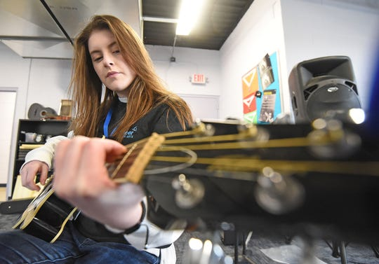 McKenna Stoffer, 17, an Ontario junior, attending Pioneer Performing Arts, practices guitar Tuesday morning at Theatre 166 building.
