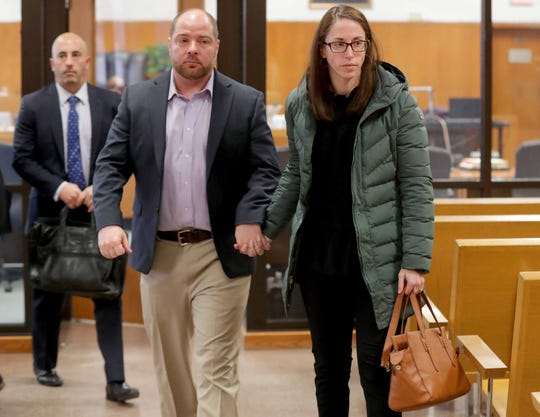 John Cox, left, a pediatric doctor  formerly at Children's Hospital of Wisconsin, leaves court with his wife, Sadie Dobrozsi, also a doctor, after Cox appeared in a Milwaukee County court in Milwaukee.