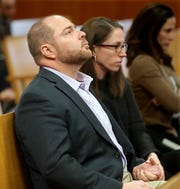John M. Cox, left, a pediatric emergency room physician, sits in court with his wife, Sadie Dobrozsi, also a pediatrician.