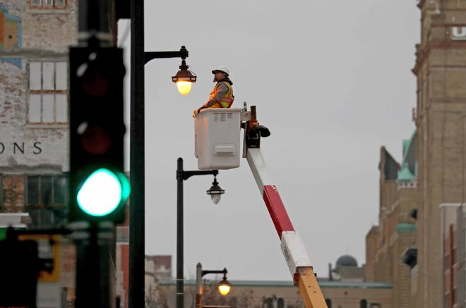Sean Gilles, an electrical mechanic with the City of Milwaukee, changes a bulb on a streetlight along North Old World 3rd Street in Milwaukee on Jan. 28, 2020.
