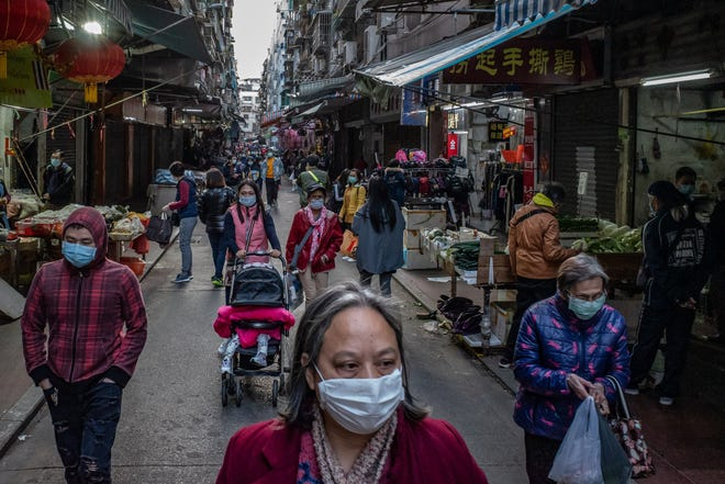Residents wearing face masks shop at a market in Macau, China, in January as cases of coronavirus continued to increase. The U.S. Centers for Disease Contol and Prevention says that Americans should prepare for disruptions in the U.S. caused by the virus.