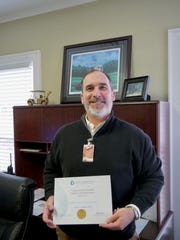 Daryl Altic, Director of Quality Assurance, hold the Louisiana United Methodist Children and Family Services' certification from the EAGLE Commission.