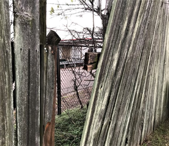 A gap in the fence behind Reginald Glover's home behind the old Kmart building on East South Boulevard.