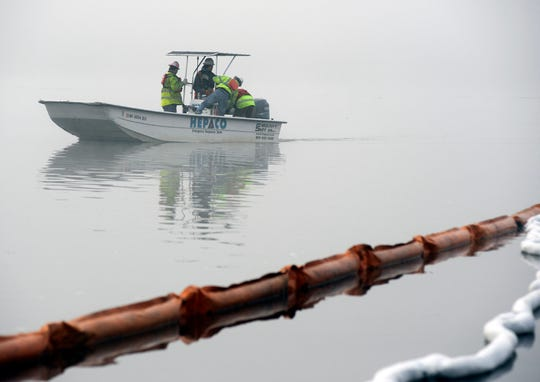 A boat motors through fog near a protective boom in a creek near the Tennessee River at the scene of a fatal marina fire in Scottsboro, Ala., on Tuesday, Jan. 28, 2020. The boom was installed to contain fuel and chemicals following a dock blaze that killed eight people at Jackson County Park Marina.