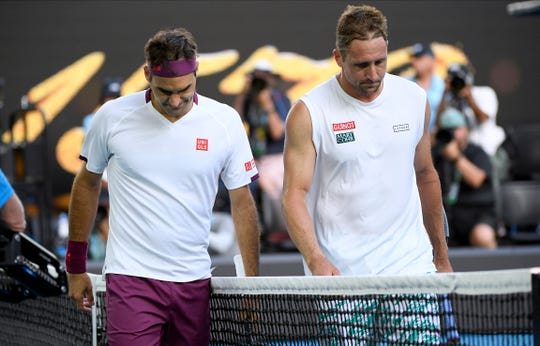 Roger Federer, left, walks with Tennys Sandgren after winning their quarterfinal match at the Australian Open on Jan. 28.
