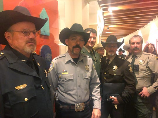 A group of New Mexico sheriffs stand outside the New Mexico Senate in Santa Fe, N..M., on Tuesday, Jan. 28, 2019, before a committee debates proposals on gun control and legalizing marijuana.